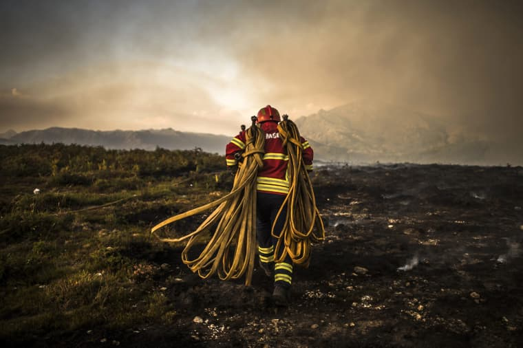 Image: A firefighter works at the scene of a wildfire in Vila do Soajo