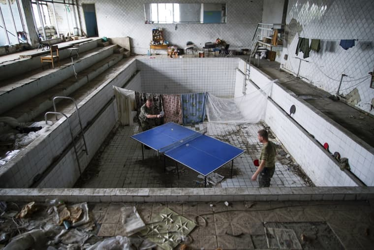 Image: Ukrainian soldiers play table tennis at a damaged swimming pool in the village of Marinka