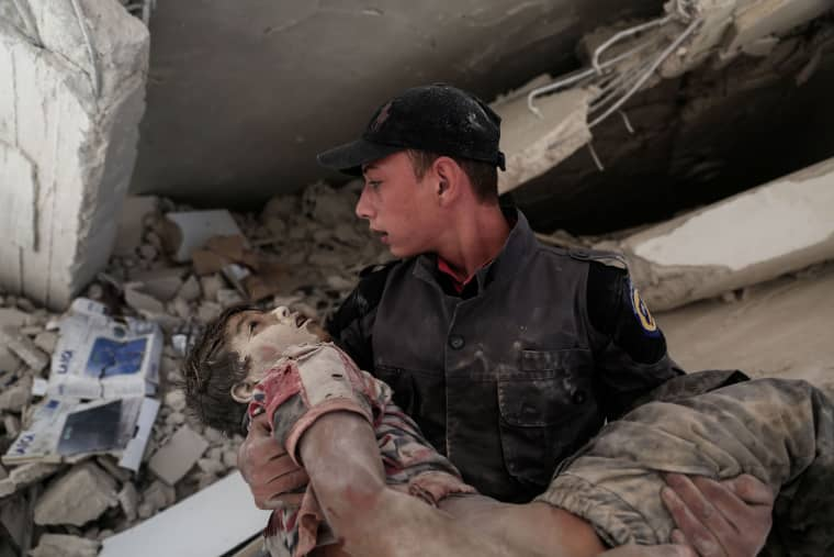 Image: A young Syrian rescue worker carries a wounded boy away from the rubble of a building in Douma, Syria