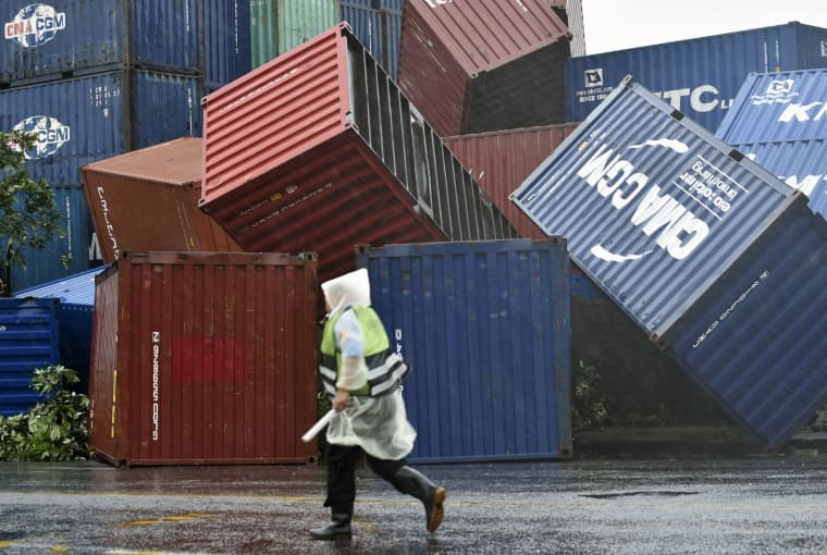 Image: A man walks past downed shipping containers at the Kaohsiung Harbor