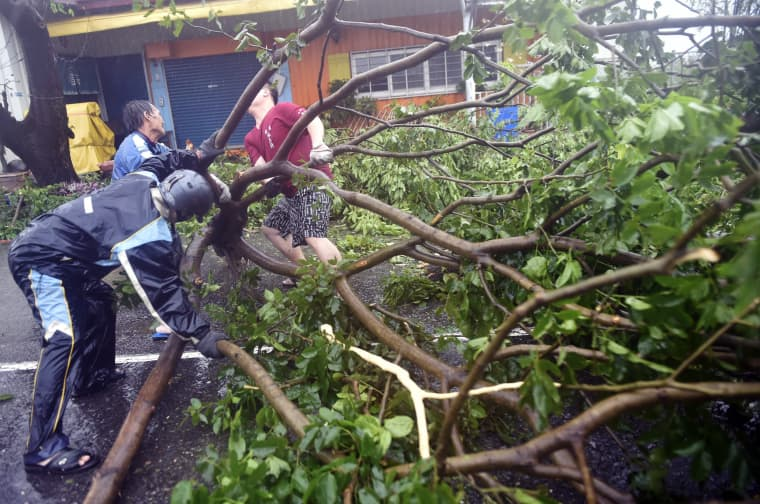 Image: Local residents help clear fallen trees from the streets