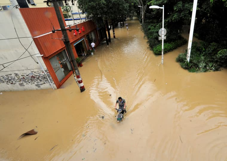 Image: A man rides through a flooded street after Typhoon Meranti made landfall on southeastern China, in Fuzhou