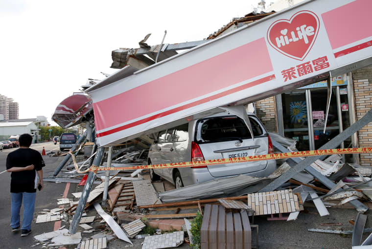 Image: A man stands in front of a damaged vehicle and convenience store after Typhoon Meranti made landfall, in Kaohsiung