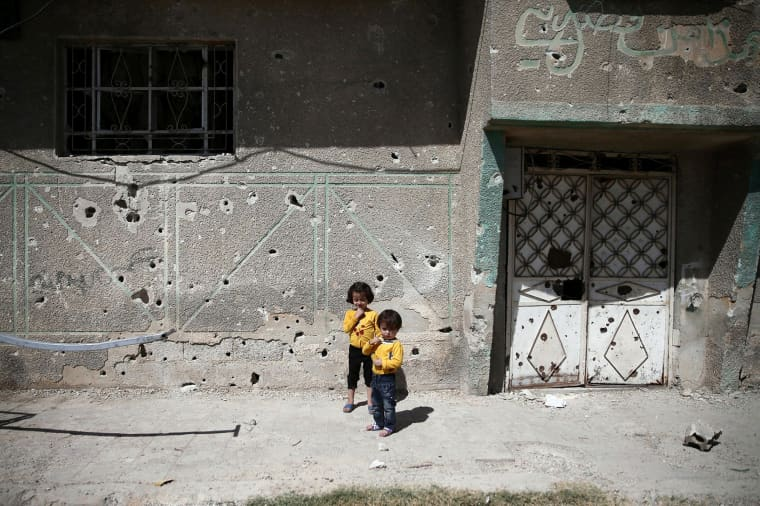 Image: Children stand in front of the bullet-riddled facade of a building in the rebel-held Douma neighbourhood of Damascus