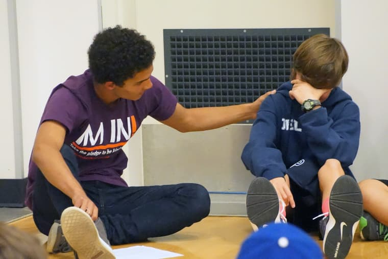 A student comforting another in a Beyond Differences demonstration.