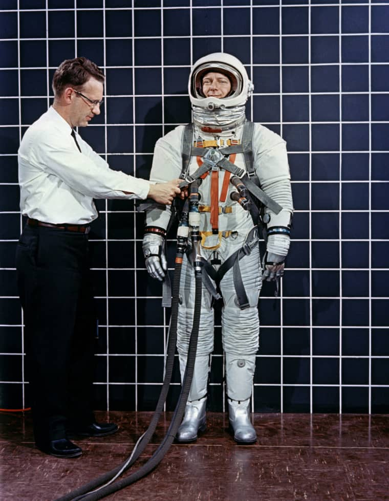 Engineer Bill Peterson fits test pilot Bob Smyth in an Apollo space suit with a Lunar Excursion Module restraint harness during suit testing in 1968.