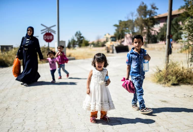 Image: Syrian refugees walk on their way back to the Syrian city of Jarabulus