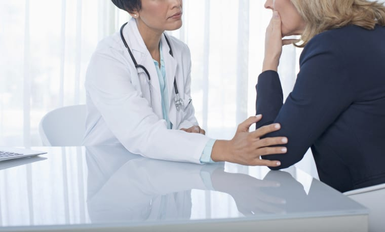 Female doctor consoling sad woman at desk in office