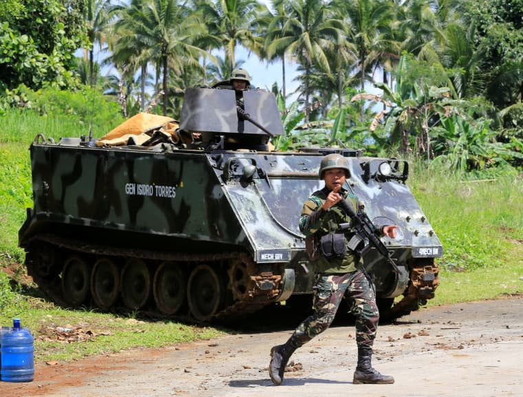 Image: A government troop gestures as he passes an armored personnel carrier posted along a main highway of Pantar town, after residents started to evacuate their hometown of Marawi city