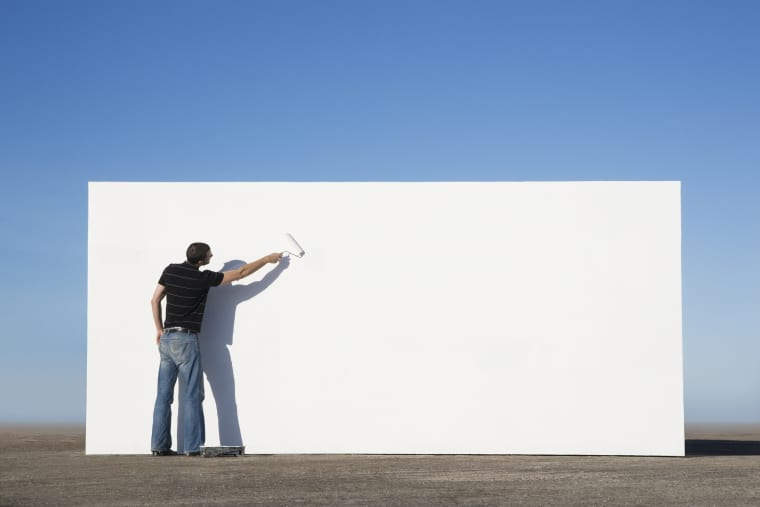 Image: Man painting wall outdoors