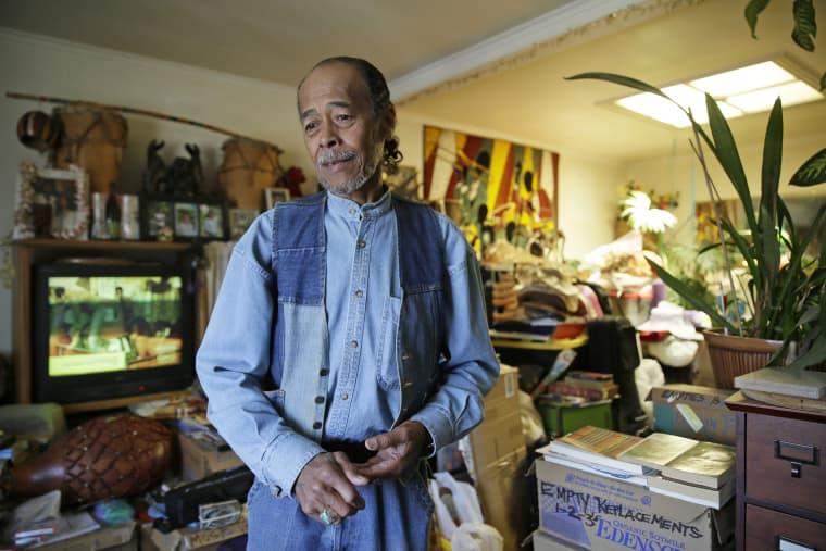 Image: Graciano de la Cruz standing in his living room
