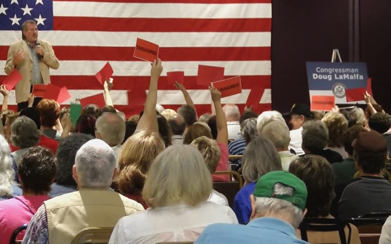 """Audience members hold up red cards that say """"Disagree"""" at a town hall in Chico, California, held by Rep. Doug LaMalfa."""