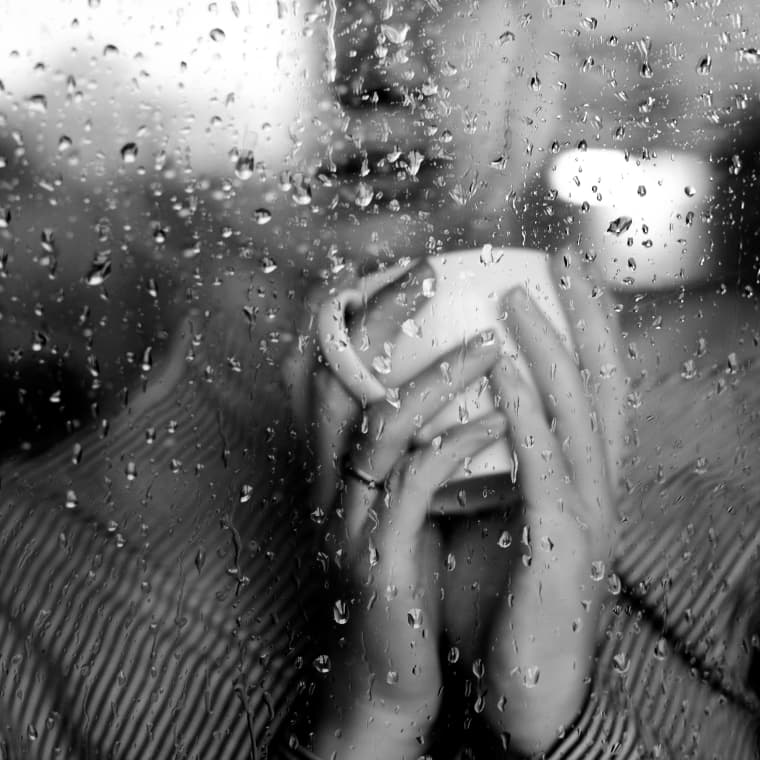 Image: A woman watches the rain from behind a window
