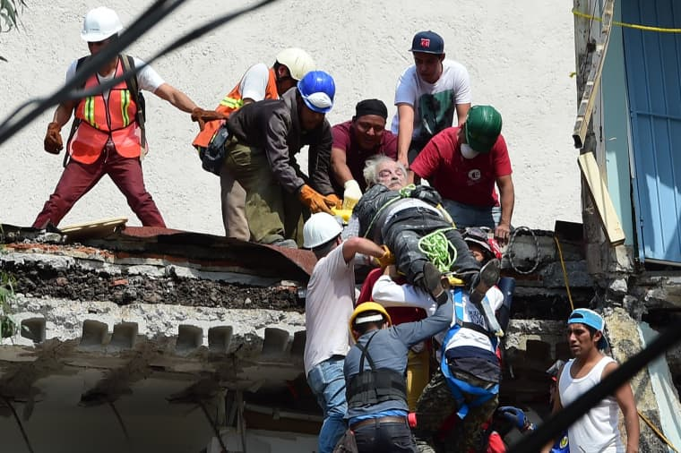 Image: A man is pulled out of the rubble alive