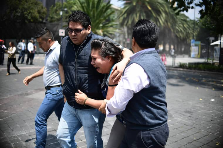 Image: A woman is comforted as an earthquake rattles Mexico City