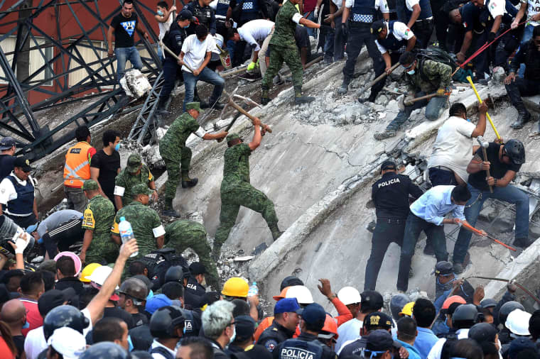 Image: Rescuers remove rubble from a building