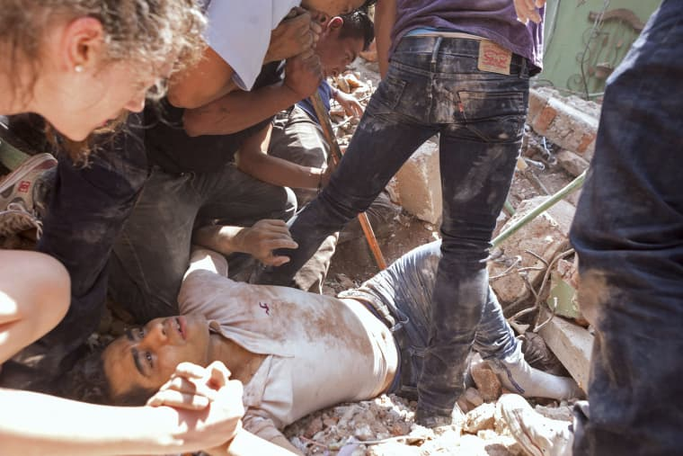Image: A man is rescued from a collapsed building in Mexico City's Condesa neighborhood