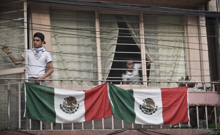 Image: Residents watch as rescuers search through rubble for survivors in Mexico City