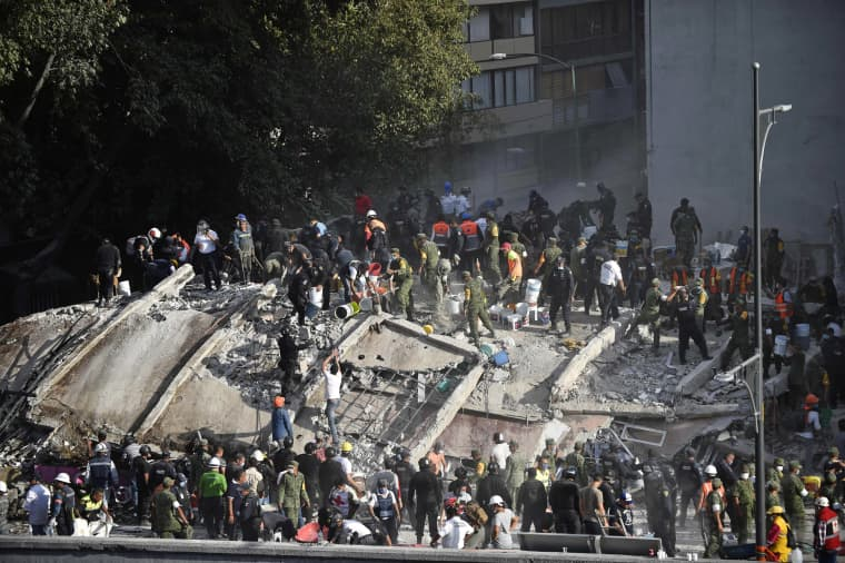 Image: Rescuers search for survivors after a building was flattened during the earthquake in Mexico City