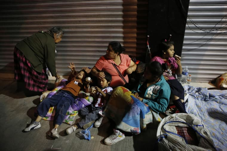 Image: Families fearing aftershocks prepare to sleep on the street in the Roma neighborhood of Mexico City