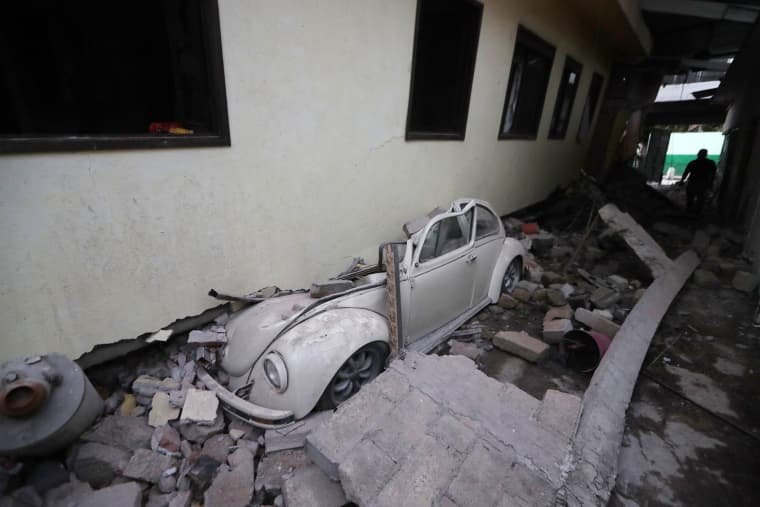 Image: A car sits crushed from a building in Jojutla, Morelos state