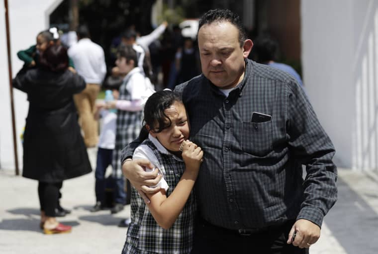 Image: A man comforts a frightened student as he picks her up from school in Mexico City's Roma neighborhood