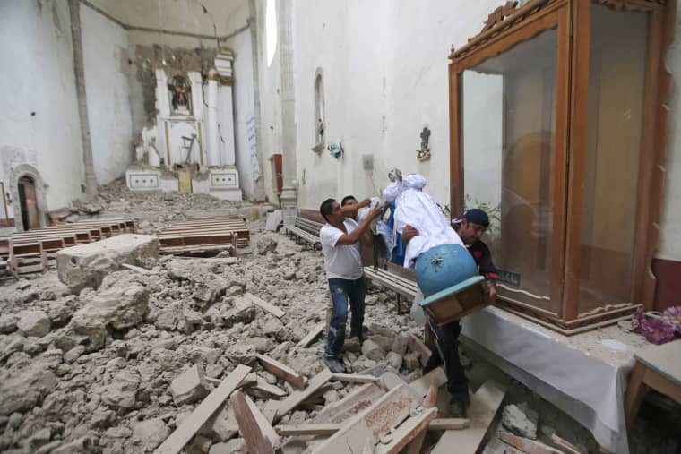 Image: Workers rescue a religious statue from the heavily damaged former convent of San Juan Bautista
