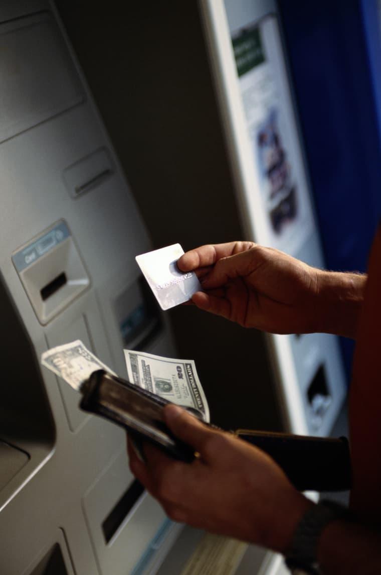 Image: A man uses an ATM machine