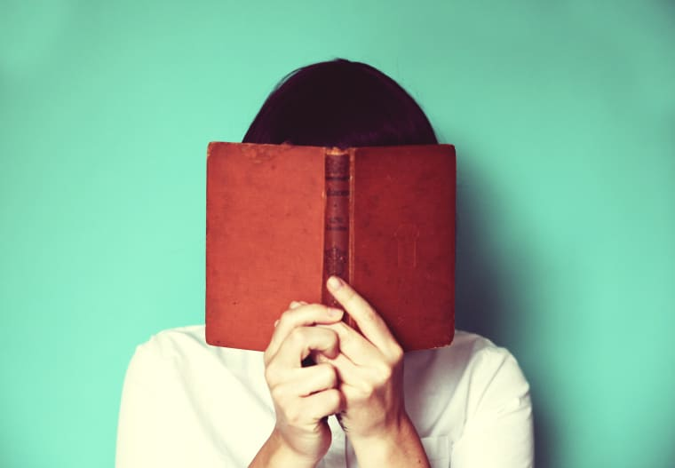 Image: A woman holds a book in front of her face