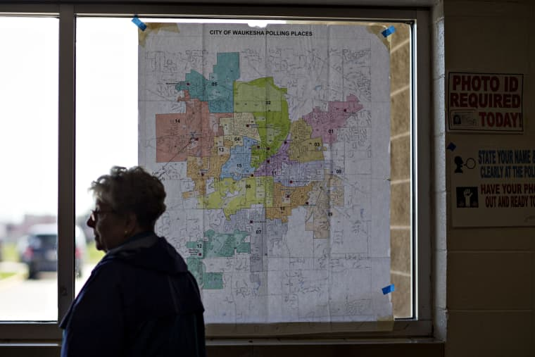 Image: A resident stands near a map of local polling places during the presidential primary vote