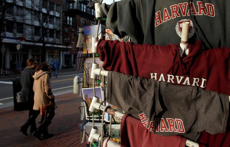 Image: People walk past Harvard University t-shirts for sale in Harvard Square in Cambridge