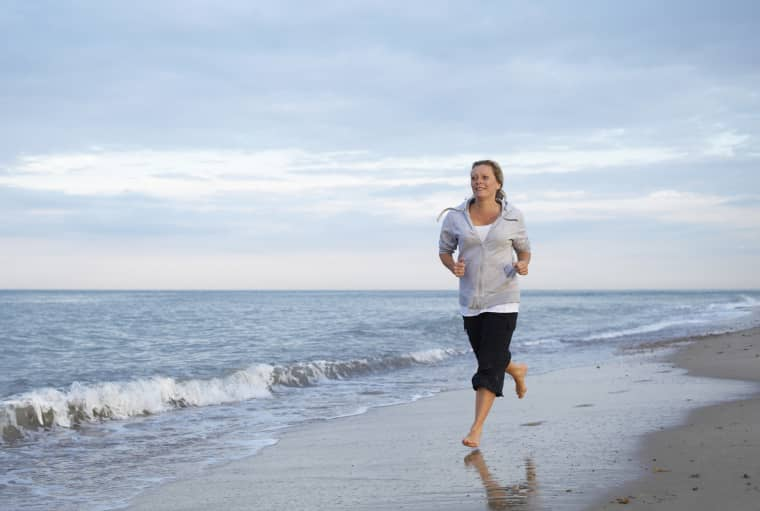 Image: A woman runs on the beach