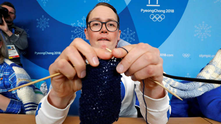 Antti Koskinen, snowboard head coach, shows how he knits, during a news conference in Pyeongchang