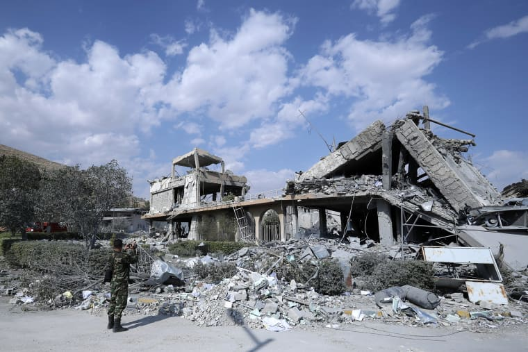 Image: A Syrian soldier films the damage of the Syrian Scientific Research Center
