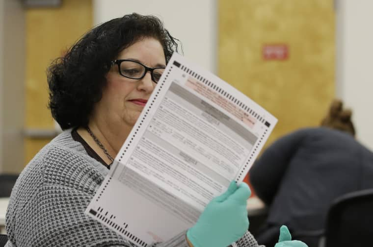 Image: An election clerk inspects a mail-in ballot