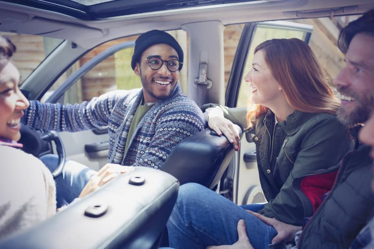 Image: Smiling friends talking and riding in car