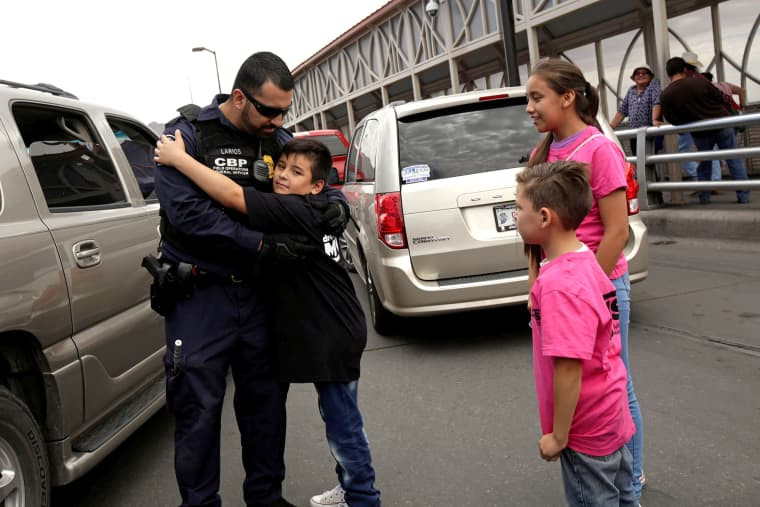 Image: A boy hugs to an officer of the U.S. Customs and Border Protection in a protest against U.S. President Donald Trump administration's immigration policies at Paso del Norte international border crossing bridge in Ciudad Juarez
