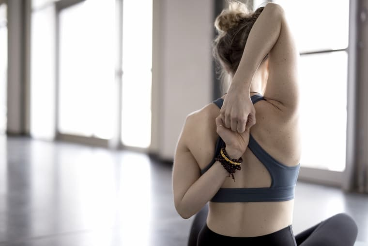 Woman practicing yoga cow face pose in gym studio