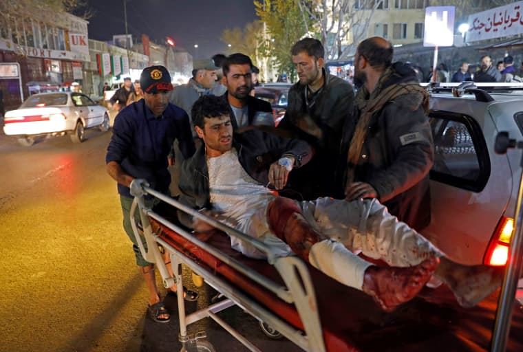 Image: Men carry an injured person to a hospital after a suicide attack in Kabul, Afghanistan