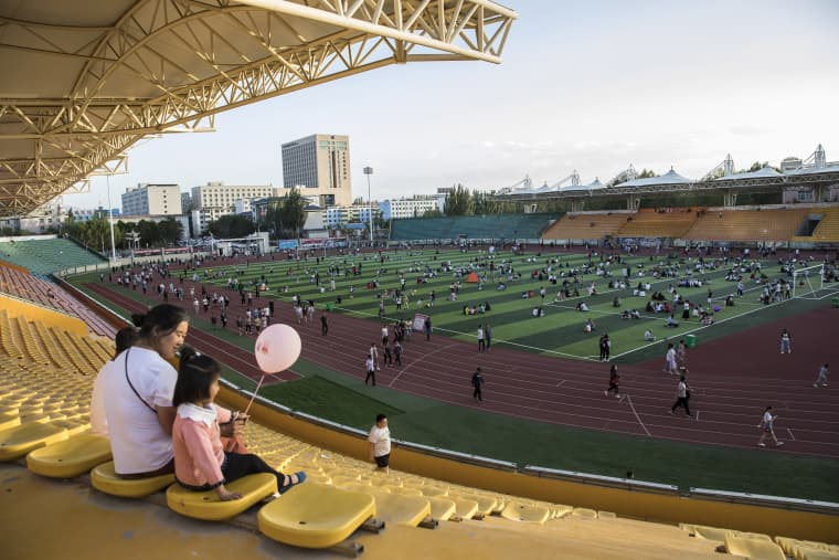 Image: A woman sits with a child holding a balloon at a sports stadium in Golmud, China
