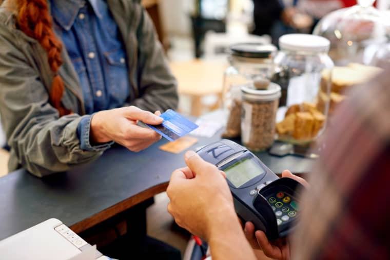 Image: A customer pays for her order with a credit card in a cafe