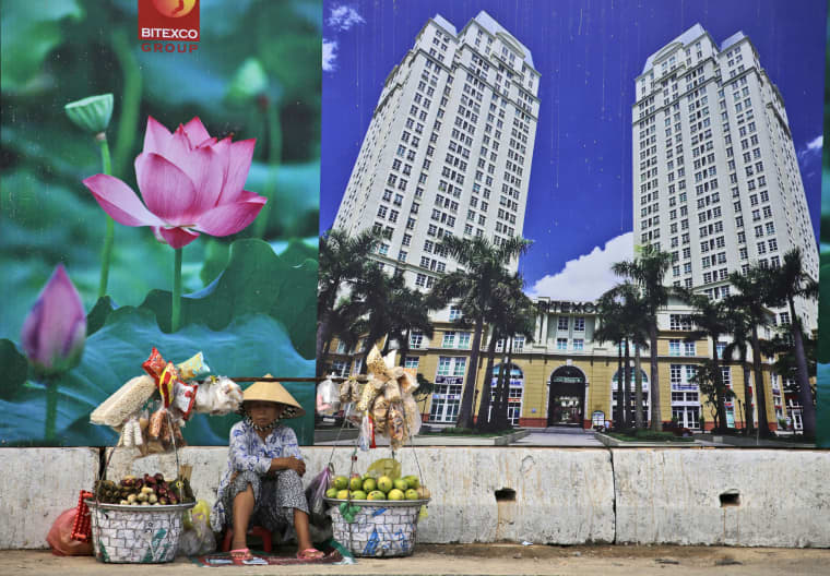 A snack and fruit vendor waits for customers near the advertisement board of a shopping mall and apartment building in Ho Chi Minh City