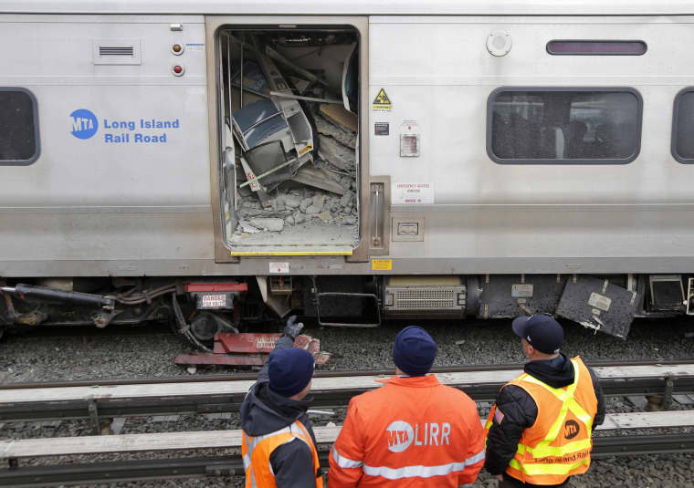 Image: Emergency personnel look over a train that derailed after striking a vehicle in Westbury