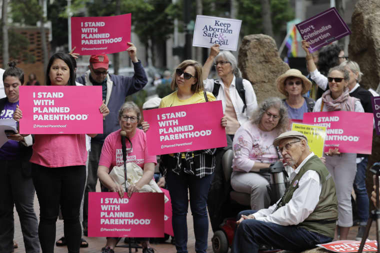 Protesters hold signs supporting Planned Parenthood in Seattle, as they demonstrate against President Donald Trump and his choice of federal appeals Judge Brett Kavanaugh as his second nominee to the Supreme Court, on July 10, 2018.