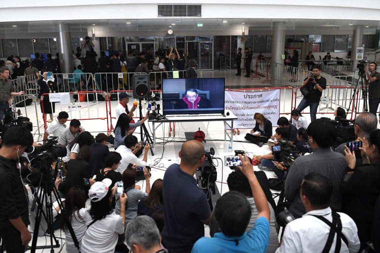 Image: Journalist records a live TV broadcast of a judge delivering the decision of the Constitutional Court in Bangkok to dissolve the Thai Raksa Chart party