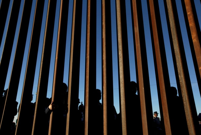 People gather on the U.S. side of the border fence between Mexico and the United States during an inter-religious service against President Trump's border wall, in Ciudad Juarez