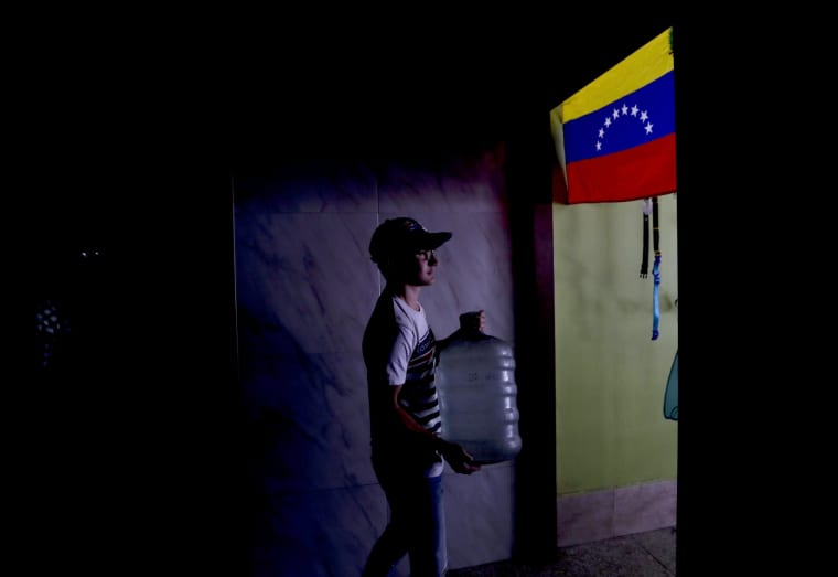 Image: David Rincon carries water from his pet shop to a woman who does not have water at her home in Caracas, Venezuela, on March 26, 2019.