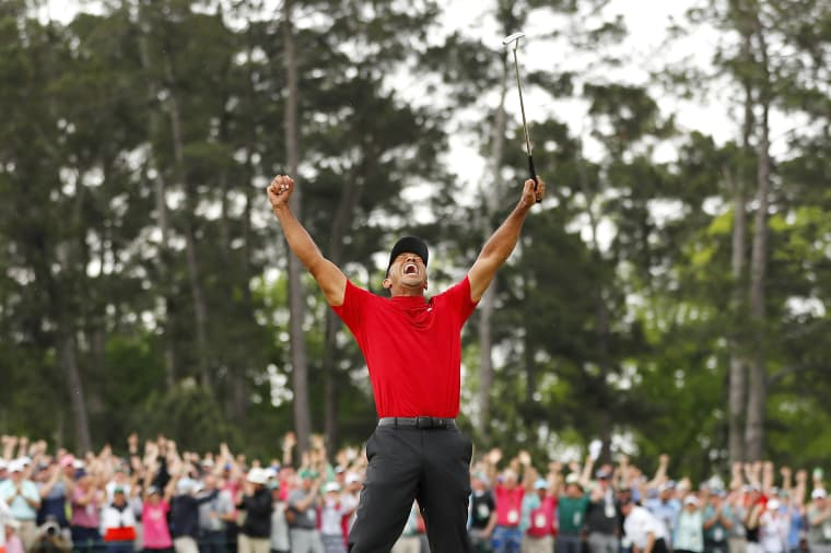 Image: Tiger Woods celebrates after sinking his putt on the 18th green
