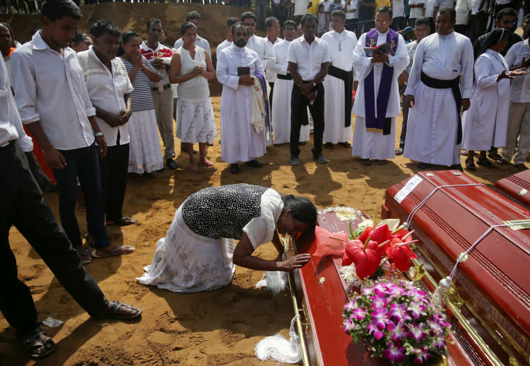 Image: A woman reacts next to a coffin during a mass burial of victims at a cemetery near St. Sebastian Church in Negombo