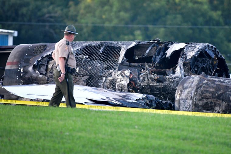 Image: A police officer walks past the wreckage of a plane crash involving NASCAR driver Dale Earnhardt Jr. and his family, who survived the incident, in Elizabethton